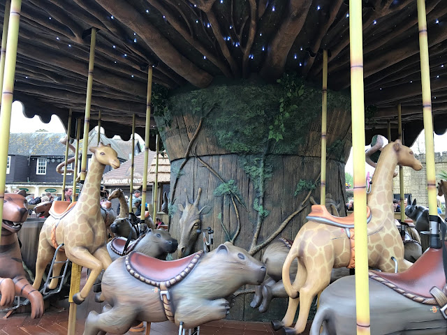 A view of a carousel with giraffes and a large rodent to sit on