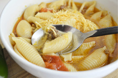 close up of bowl of taco soup with pasta and cheese