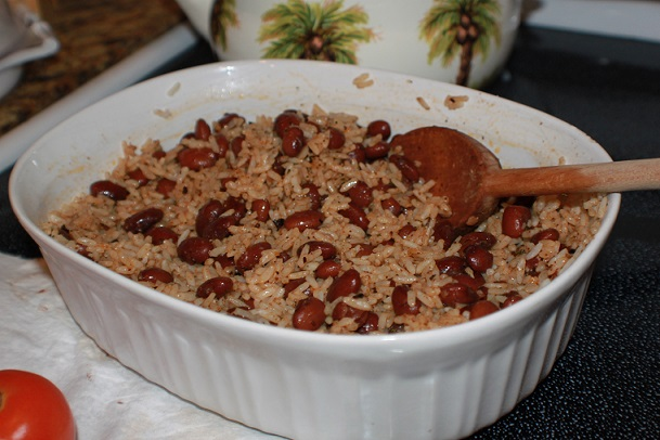 this is a simple rice and red beans meal in a white bowl with a big spoon in it