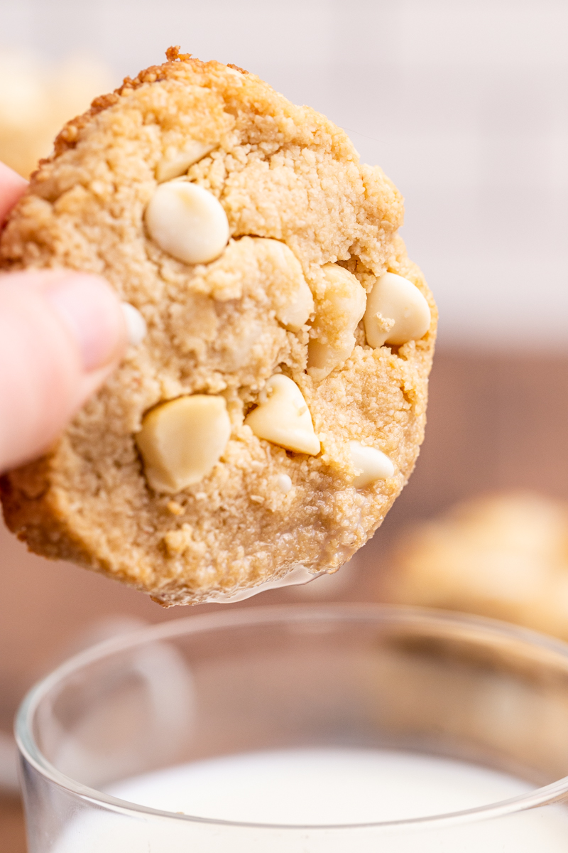 Closeup photo of a Keto White Chocolate Macadamia Nut Cookies being dipped into a glass of milk.