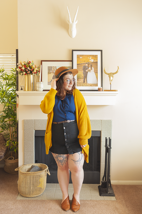 An outfit consisting of a brown panama hat, mustard yellow chunky cardigan, navy blue blouse tucked into a black button down skirt and brown d'orsay flats.