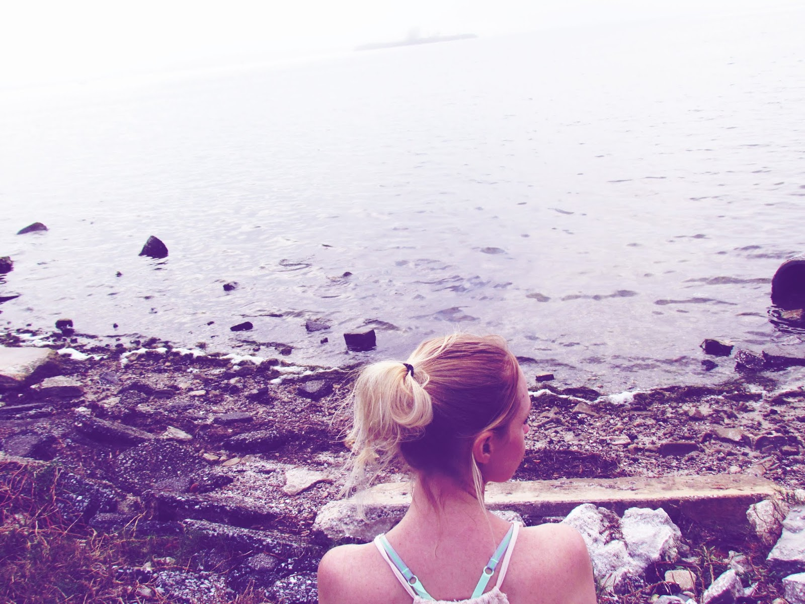 Blonde Woman With Ponytail Sitting on a Rocky Beach Overlooking Tampa Bay in Winter