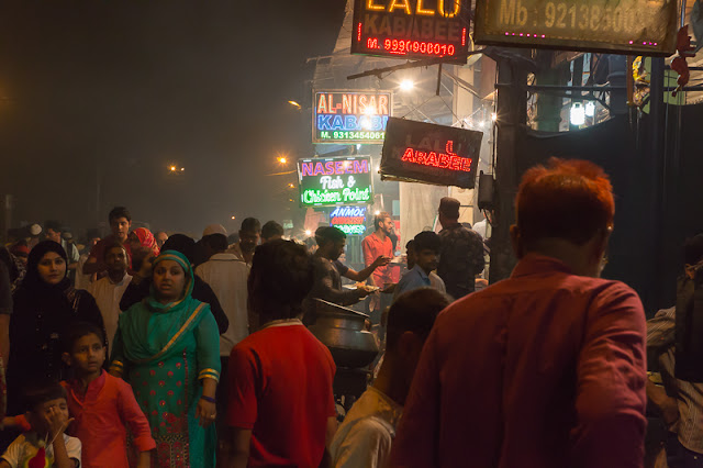street food stalls with people opposite Jama Masjid Old Delhi in India