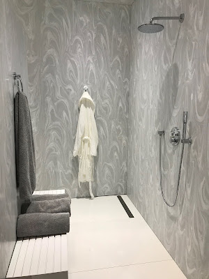 Grey walls of a large shower. On the farthest wall hangs a white, bathrobe. One the wall opposite of the showerhead, lies a bench with two, grey towels resting on it, and a grey towel hanging over it.