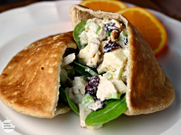 Waldorf Style Chicken Salad inside pita cut in half, on white plate