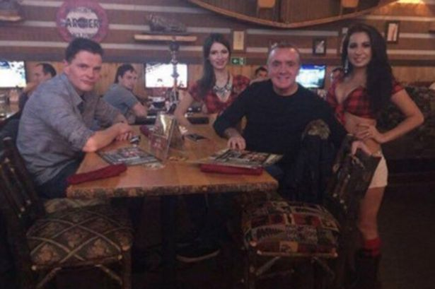 Young fans: Liverpool chief executive Ian Ayre poses with bikini-clad barmaids