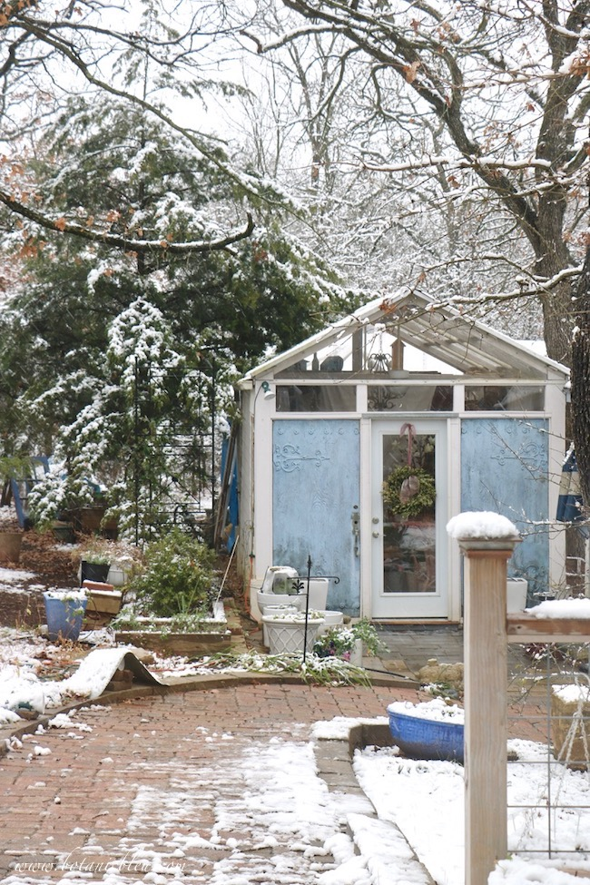 A greenhouse adjacent to the beautiful blue and white French Country garden shed has little snow on its roof