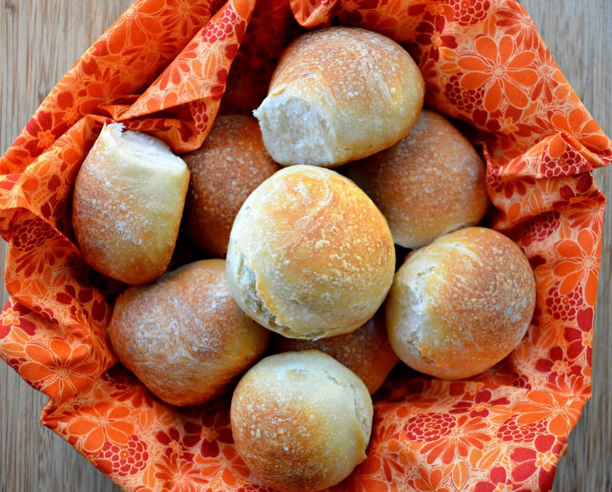 A basket lined with an orange flower cloth filled with French Bread Dinner Rolls on a bamboo cutting board.