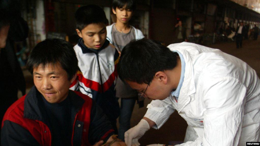 Un trabajador médico chino sustrae sangre a un vendedor de gatos para consumo humano en Guangzhou, en el sur chino. Un virus similar al SARS fue encontrado en un gato que había sido vendido en mercados locales como