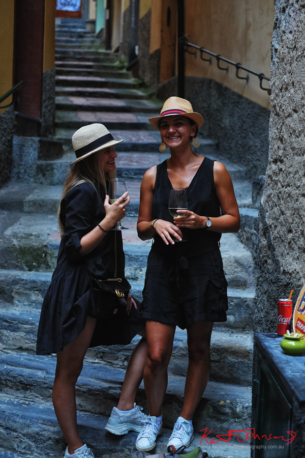 Two stylish, hat wearing travellers in black summer outfits - Vernazza, Cinque Terre, Italy - Photographed by Kent Johnson for Street Fashion Sydney.