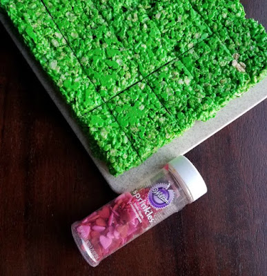 green rice krispie treats with bottle of candy hearts
