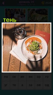 на столе блюдо и рядом показана тень от рук которые хотят взять тарелку и бокал