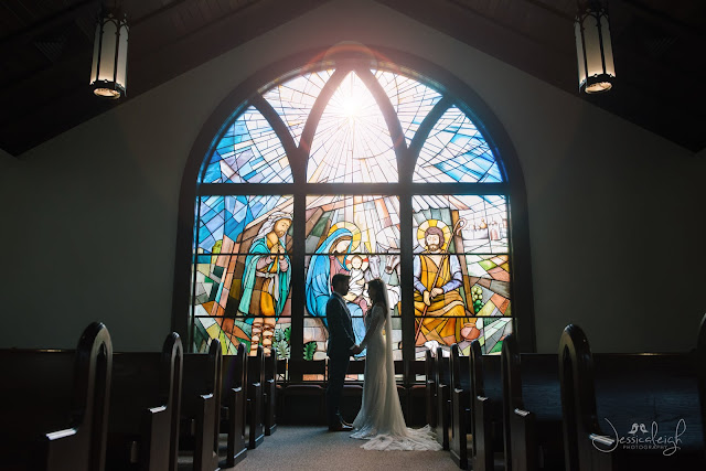 bride and groom in shadow of chuch stained glass