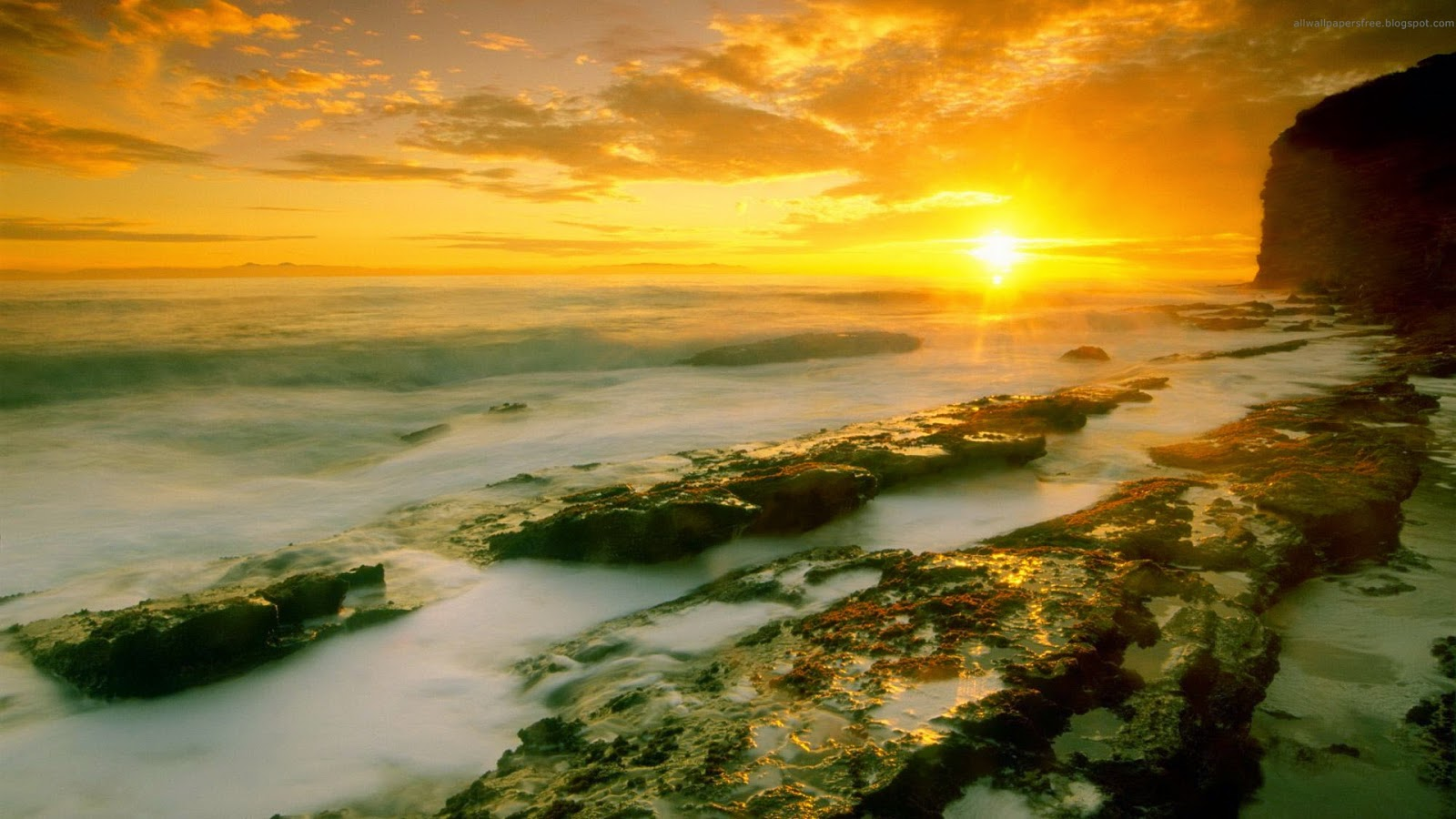 Wallpaper met natte rotsen bij zonsondergang