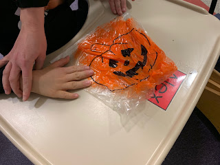 hands holding large ziploc bag with jack-o-lantern outline and orange paint inside on top of attached tray