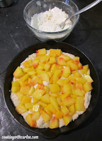 cast iron skillet with cake batter and chunks of peaches ready to be baked into a coffee cake