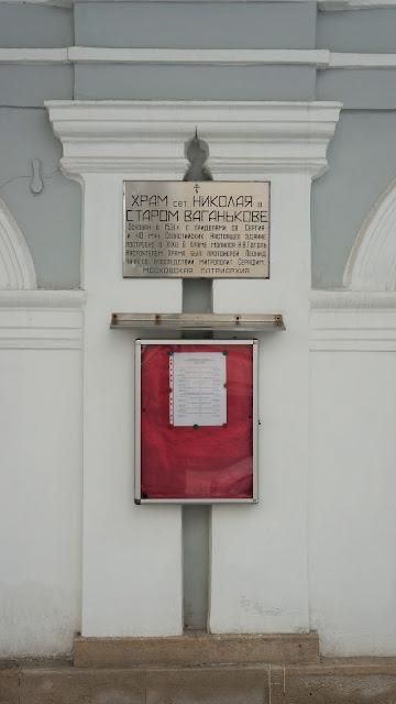 На фото - Табличка с названием храма и доска с расписанием богослужений