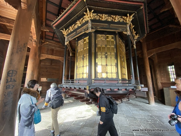 visitors push prayer wheel in Kyozo at Zenkoji Temple in Nagano City, Japan