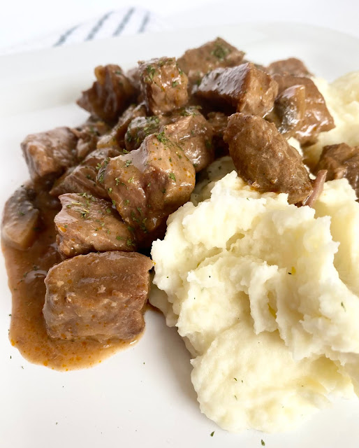 Dutch Oven Steak Diane...a new twist on the classic! Tender stew meat is cooked low and slow with onions, mushrooms, tomato paste, red wine, beef stock and more. Serve with mashed potatoes!