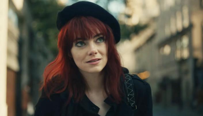 Imagem: a personagem Estella, interpretada por Emma Stone, uma moça de cabelos vermelhos com uma boina preta e um casaquinho preto combinando, em uma rua de Londres.