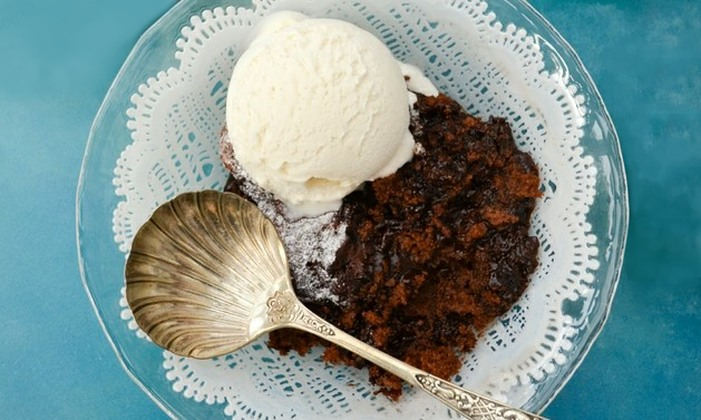 Self-saucing chocolate pudding in a glass bowl with a scoop of vanilla ice cream