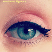 Black eyeliner with a flick, green eyes and peach eyeshadow. Small wing cat eye, lift down turned eyes.