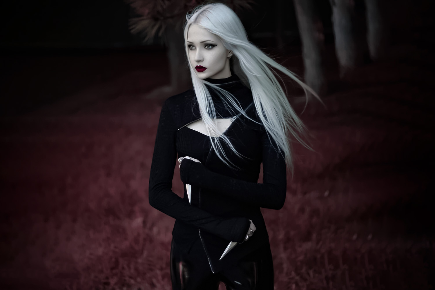 gothic woman with long blond hair in the forest