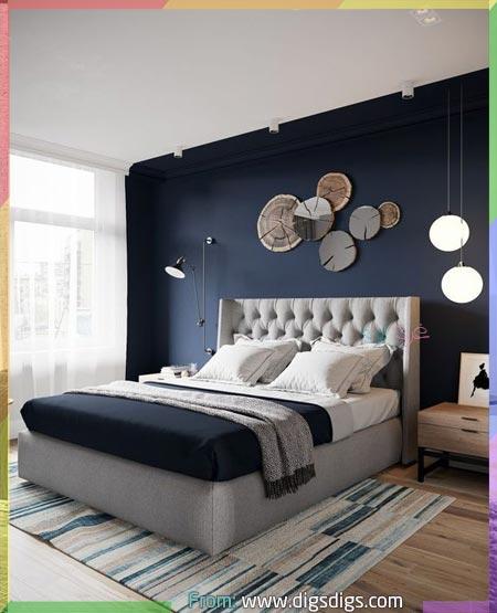 جدار غرفة رئيسي بالأزرق والسرير باللون رمادي