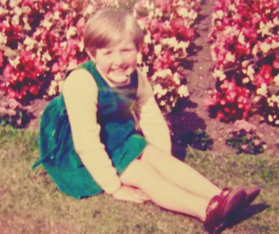 "An old photo, from the 1980s, of a young girl about 5 years old. She is sitting on the grass, rows of red and white flowers behind her. She is looking into the camera and smiling. She has short hair, in a pixie cut, and is wearing a green pinafore dress over a white long sleeved shirt. She is sitting with her legs stretched out, her hands tucked under her knees. She is wearing red patent dolly shoes. Image for ""Teaching your children about online privacy"""