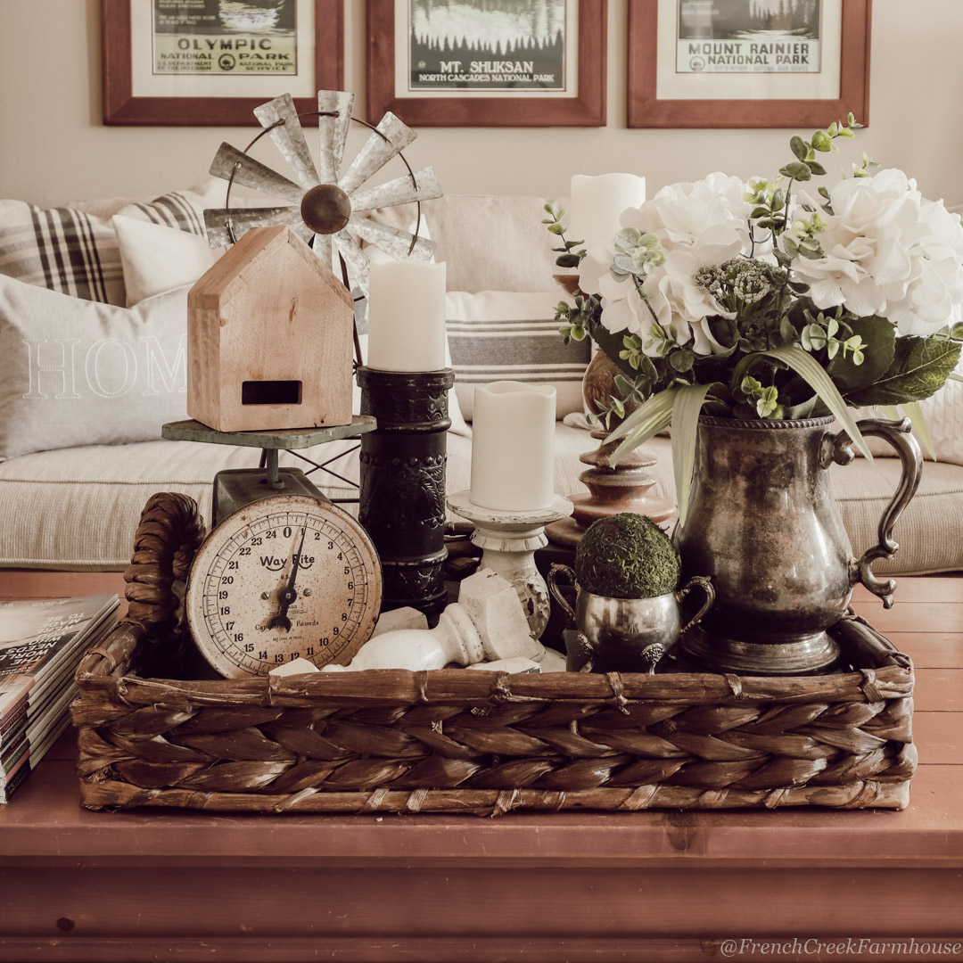 Farmhouse coffee table decor with faux white hydrangeas in a vintage silver pitcher