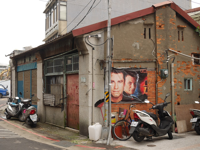 Portion of Broken Arrow movie poster with John Travolta and Christian Slater on a building's wall