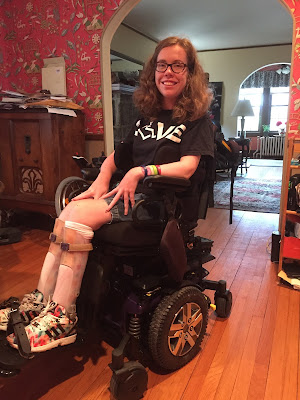 "Kathleen sitting in her wheelchair wearing a 3E Love shirt that says ""Love"" with a ""wheelchair heart"" as the O"