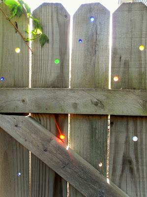 Cerca de madera con adornos de vidrio reciclado.