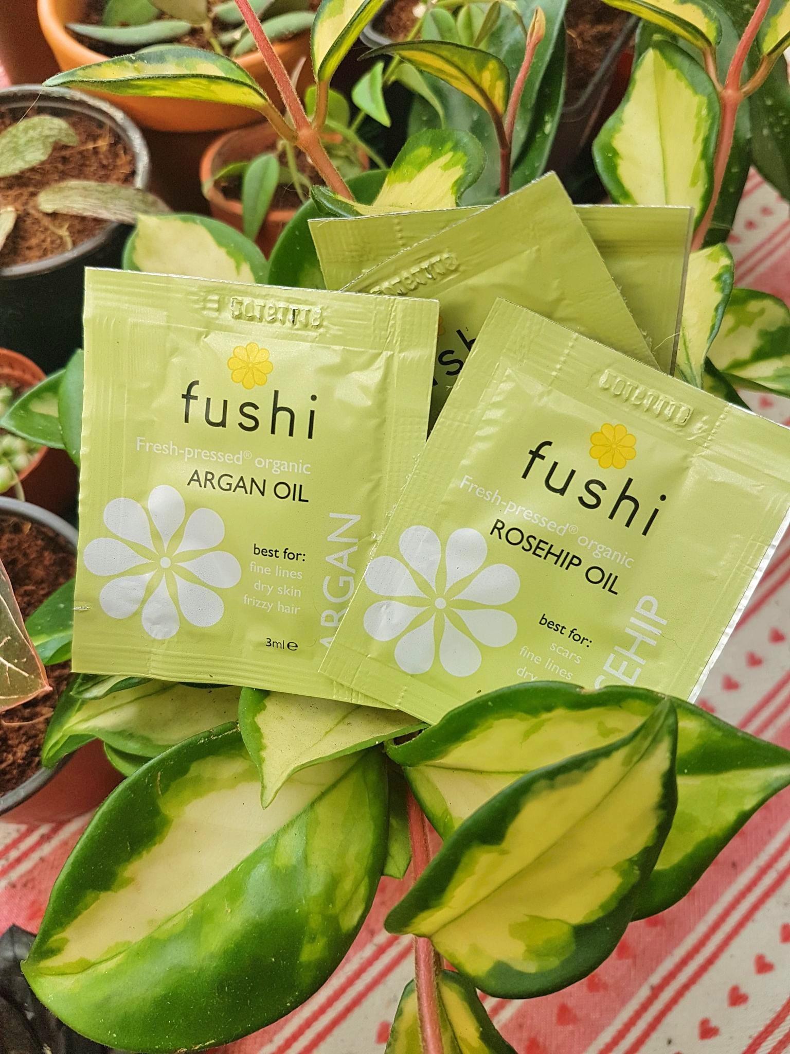 Fushi rosehip and argan oil plastic sample sachets sitting on a hoya plant
