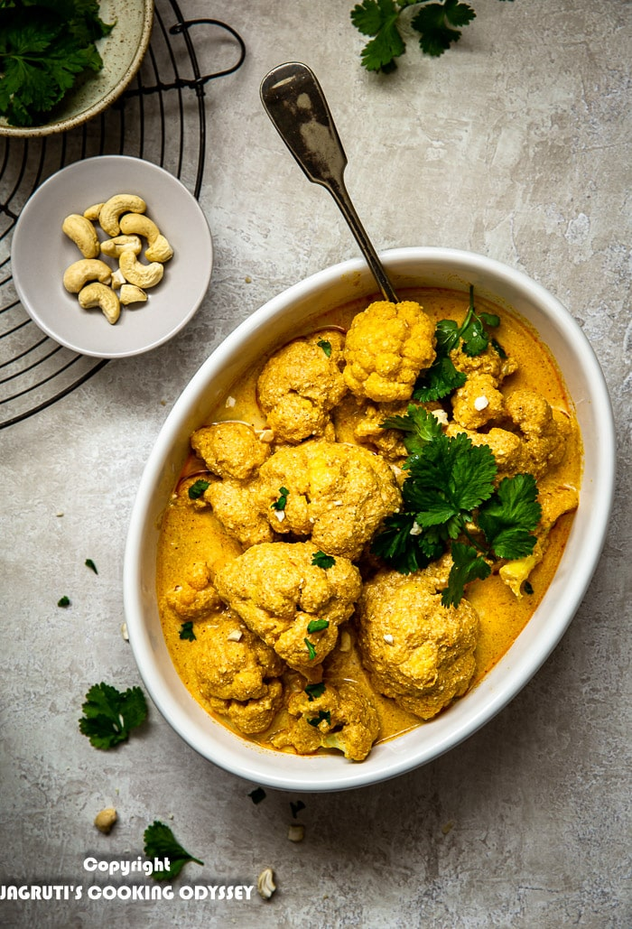 Instant pot vegan cauliflower korma served in a white oblong dish next to a bowl of cilantro.