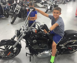 Childhood picture of Kaleo Browne sitting in a bike