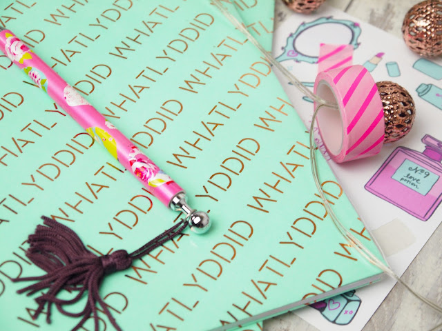 a notebook wrapped in mint paper with 'whatlyddid' printed on it in copper foil, with a pink pencil atop the book