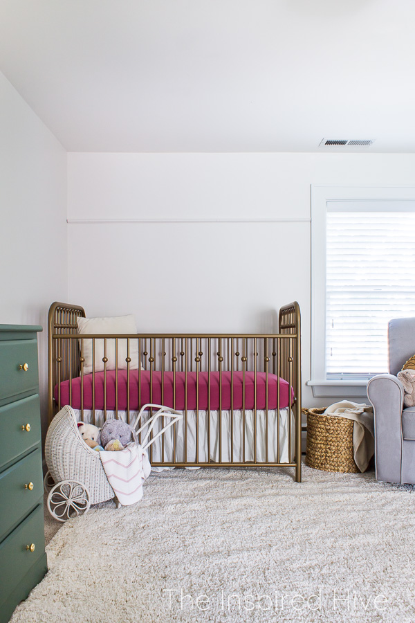 Pink and green modern traditional girl's nursery with gold crib and green dresser