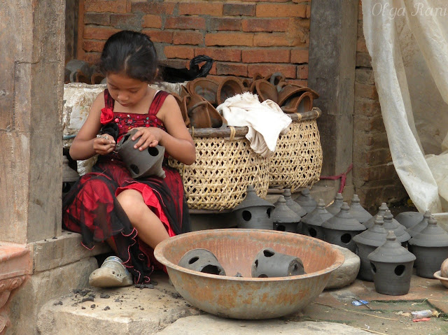 Small Nepali girl helps with creating pottery