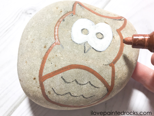 painting the outline of an owl on a rock with a brown posca pen