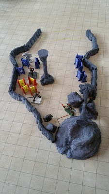 A tunnel entrance 30 feet wide, opening to 50 feet, before narrowing down to 20 feet. The tunnel is blocked with a cart under rubble 70 feet from the entrance. 12 goblins in 3 groups of 4 are clustered along the walls