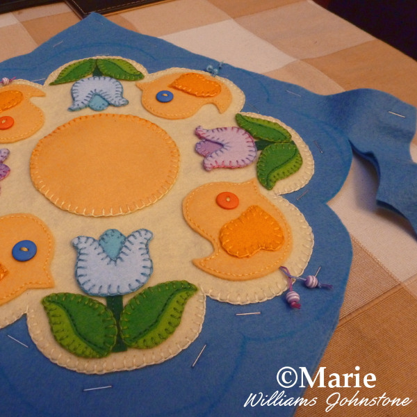 Sewing the Easter Spring themed candle mat up onto another layer of felt
