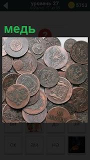 На столе рассыпаны старинные монеты сделанные из меди с различными изображениями из прошлого