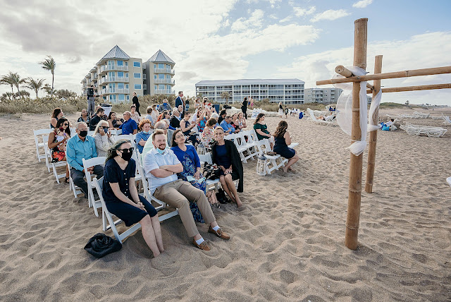 Guests sitting at beach side wedding with wind blowing