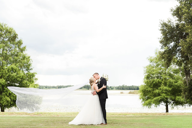 bride and groom kissing at lake mary events center lake