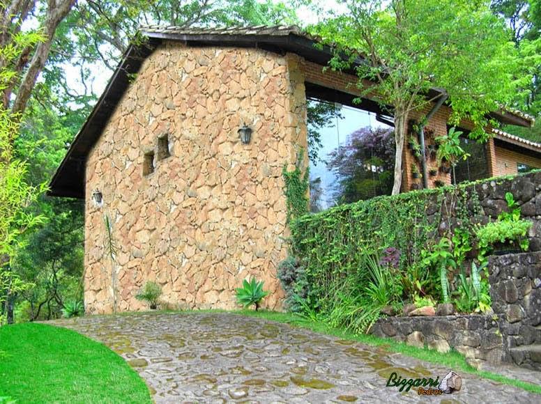 Parede de pedra moledo assentada tipo duas faces em construção de residência com os muros de pedra, o calçamento de pedra e a execução do paisagismo.
