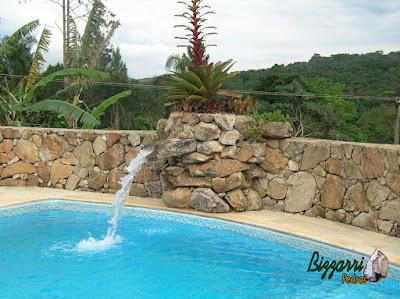 Construção de muro de pedra com pedra bruta com a construção da piscina de vinil, a cascata de pedra com a bica d'água de madeira em sítio em Mairiporã-SP.