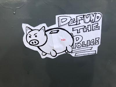 """Pig bank sticker, """"Defund the Police"""" written next to it."""