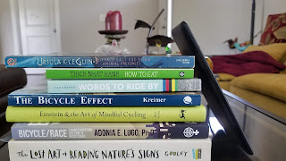 Stack of books with Kindle leaning up against the right side of the stack, red candle on tall candle holder in background. Book titles mostly about bicycling.