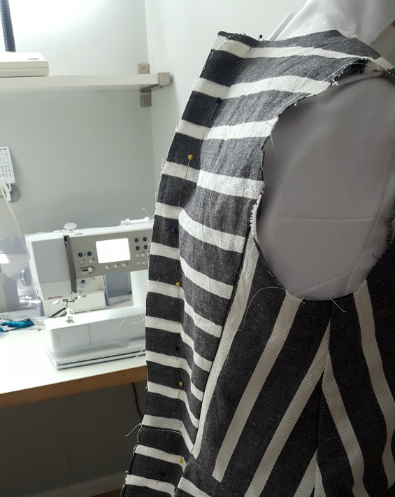 image showing a partially constructed stripe dress with pins down the centre back